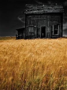 Abandoned old black farm house, black sky