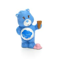 """This vintage Care Bears miniature figurine is """"Grumpy Bear Dropping Ice Cream on His Foot."""" Grumpy Bear is blue with a rain cloud on his tummy and is holding an ice cream cone. There's a pink scoop of"""