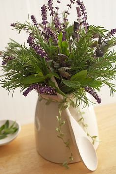 .Fresh herbs arranged in a cute crock with wooden spoon