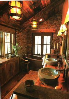 Rustic bathroom with stone walls and sinks, reclaimed wood, and copper tub