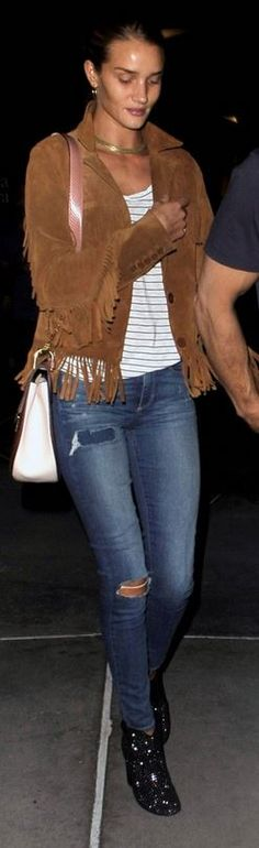 Brown suede fringe jacket, colorblock handbag, studded black boots, and ripped skinny blue jeans