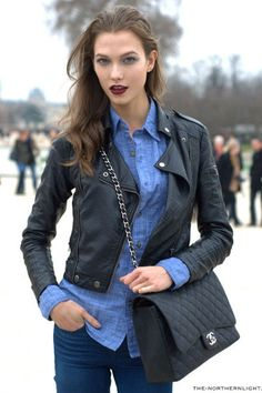 Karlie Kloss in A black leather jacket over a chambray collared shirt and paired with blue Jean pants. Dark plum lips and black, leather, quilted purse. Models off-duty. Model street style.