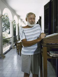 Hemingway working on the porch of friend Bill Davis' house in Malaga, Spain. Davis provided the desk for Hemingway and most likely took this photograph.
