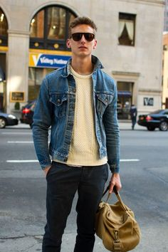Try pairing a blue denim jacket with charcoal chinos for a refined yet off-duty ensemble.  Shop this look for $98:  http://lookastic.com/men/looks/sunglasses-cable-sweater-denim-jacket-chinos-holdall/7623  — Dark Brown Sunglasses  — Beige Cable Sweater  — Blue Denim Jacket  — Charcoal Chinos  — Tan Leather Holdall
