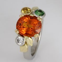 Ring palladium, 18ct yellow gold and 18ct green gold featuring a manderine garnet as the main stone and a tsavorite garnet and a mali grossular garnet and a diamond.