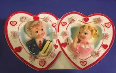 """Darling rare Relpo twin heart boy and girl Valentine planter. Minor red cold paint loss on top of rim above boy on hearts edge (see pictures). 7"""" wide x 4"""" tall. Does have some smutz inside and scuffs on bottom sitting edges. Black straight mark on bottom is not a crack. Pretty bright colors. Boy offering girl a Valentine gift!   eBay!"""