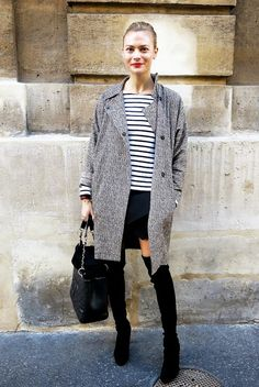 Pandora Sykes wears a striped shirt, gray coat, mini skirt, thigh-high suede boots, and a quilted Chanel tote bag