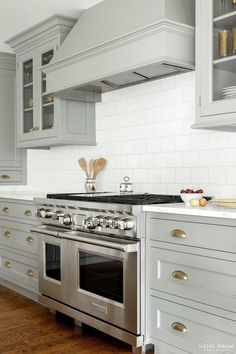 Kitchen with Light Gray Cabinets and Covered Range Hood - Heidi Piron Design