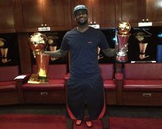 LeBron James holding the 2012 NBA championship trophy and his 2012 NBA Finals MVP trophy.