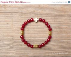 ON SALE Garnet & Gold Single Cross Beaded Gemstone Stretch Bracelet by AwenJewelry, $24.00 - Our trendy gemstone stretch bracelet features 8mm round, deep red, faceted garnets with gold plated cross and barrel beads. 8 inches around, this stretch bracelet will comfortably fit wrists up to 7-3/4 inches.