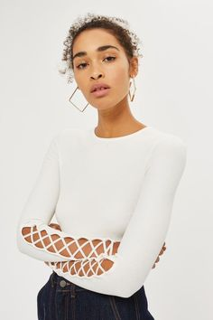 Cropped length long sleeve top with lattice detailing on the sleeve.