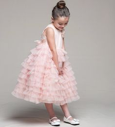 Ruffled Flower Girl Dress in PinkRuffled Satin & Organza Flower Girl Dress This beautiful peachy pink flower girl dress is just a touch more saturated than blush pink and works well with shades of blush, coral, and garden pinks. The dress is available at this time in girls sizes 2 to 10 and comes in three popular colors. The ruffles are soft matte organza with an additional built in crinoline slip underskirt.
