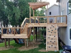 Patio with a slide and rock wall ----- New Cedar Deck with Slide and Rock Wall | Des Moines Deck Builder - Deck and Drive Solutions