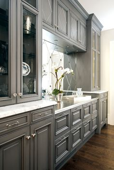 Great grey colour with the marble counter top paired with the warm brown wood tones.