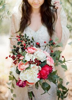 Something Blue Magazine - Christmas Wedding Ideas, a stunning bouquet featuring beautiful bright hues of red among wild green foliage. #peonies #wedding #bouquet #roses #christmas #red #berries