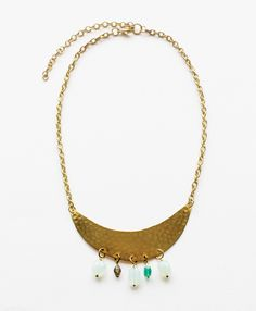 This necklace features dainty semi precious stones in shades of seafoam and jade swing from a crescent of hammered brass.