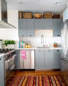 A white and gray organized kitchen with visible woven baskets above cabinets and subway tiled backsplash