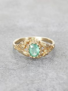 A lush Golden Garden of delicately detailed wild flowers and gracefully winding leaves, reveals a precious, crowned Emerald jewel. This would make an exceptional & unique Engagement Ring. Set in Solid