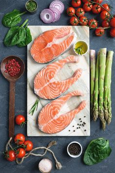 Fresh salmon steaks, herbs, olive oil and cooking ingredients on marble background by Vladislav Nosick - Photo 241157141 / Talipa Fish Recipes, Whole30 Fish Recipes, Salmon Recipes, Seafood Recipes, Oven Recipes, Fresh Seafood, Fish And Seafood, Carnicerias Ideas, Photo Food