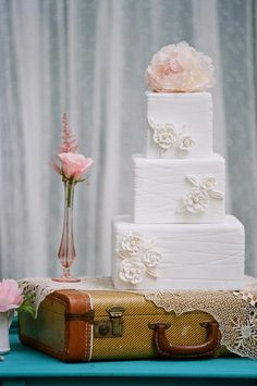 Love the cake on top of the old leather luggage.  The cake is simple yet elegant.