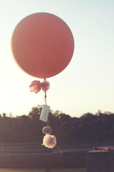 Tie pom-poms, tassels, trinkets and cards to balloons like this one from Bespoke Balloonery.