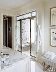 A soothing, neutral master bath is accented by boldly veined marble surfaces.