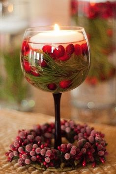Wine glass with cranberries, pine twigs, and floating candle plus a cranberry wreath for the winter wedding feel