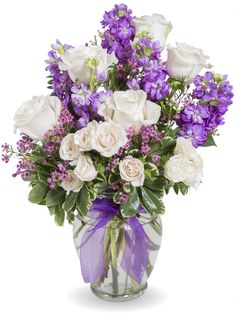 A perfect collection in shades of purple and ivory with assorted sizes of roses, fragrant chamelaucium, and a designer choice of greenery to enhance the look. A sheer purple ribbon completes this elegant one-sided funeral design.