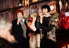 Phryne and Dr. Mac in front of a fireplace ....A Miss Fisher Christmas Special