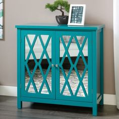 Features:  -Adjustable shelf behind door.  -Finish: Caribbean blue .  -Doors feature geometric, mirrored design.  -Inspired style.  Base Material: -Manufactured wood. Generic Specifications:  -2 shelv
