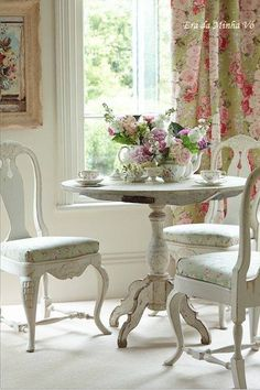 White painted pedestal dining table set for tea.  I love the fabric chair cushions and curtains!