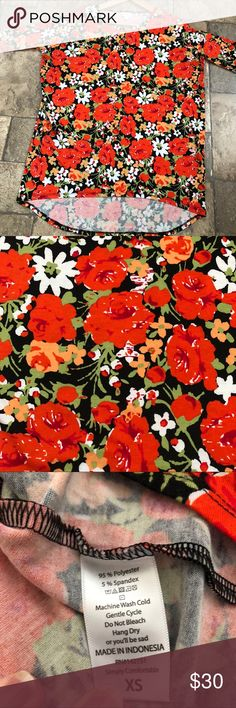 LuLaRoe Floral Irma XS This beautiful Irma is a must for your closet! High-low style makes it the perfect top to wear with leggings and jeans, but this stand-out beauty would look great with a skirt or paired with a Sarah or Joy (see last picture, Joy listed separately in my closet). This Irma has a black background with bright coral roses, salmon & white  flowers and green foliage. It's in perfect condition but I need to purge my extensive Lularoe collection. From pet and smoke free home…