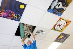 Handiman Doug Bunn, of Raleigh, stands on an 8' ladder to install hand-painted ceiling tiles at the Cancer Centers of NC Raleigh office on Macon Pond Road in Raleigh, N.C. It is part of the Healing Ceilings program that was started in June. The brainchild of Amy Jo Edwards, not seen, she has gotten artist friends to contribute. As well, she has started a Facebook campaign that has gotten paintings from as far away as Florida. Extra tiles are sent to 4 other centers in the state.