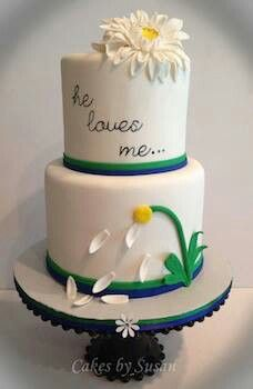 This is a beautiful white fondant engagement cake with edible decorations