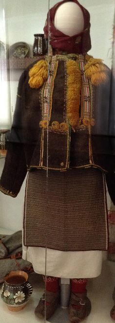 """Traditional female costume of the western part of Ukraine. This clothing was made in Rakhiv district, Transcarpathian region of Ukraine at the beginning of the 20th century. The outfit consists of a long shirt, a wrap-around skirt called """"zapaska"""", a woolen outerwear called """"serdak"""", a kerchief, woolen socks, and leather shoes called """"postoly"""""""