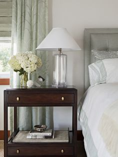 Elegant tufted headboard, crisp white bedding with gray/green border. Glass column style table lamp on rich mahogany nightstand with drawers and shelves. Beautiful pale green draperies and roman blinds.
