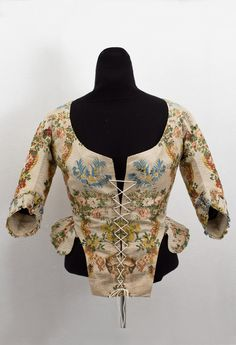 Brocaded silk caraco-style jacket, c.1780. Fashioned from plush brocaded silk damask and expertly pieced together to form perfect mirror images of the pattern in front and back. The jacket is lined with beige linen; the back peplum is lined with pale aqua silk. The center-back seam is boned.