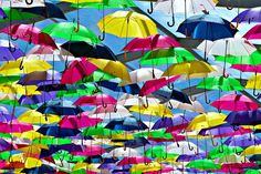 Streets in Águeda, Portugal have been covered in a colorful canopy of umbrellas and beach balls for the month of July in a recurring summer installation by Portuguese art studio Sextafeira Produções.