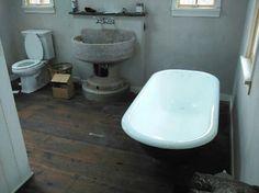 Gleaming restored tub by Dennie's Resurfacing LLC beside an original street water fountain repurposed as a sink in Upper Black Eddy PA - contactus@denniesresurfacing.com