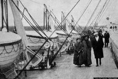 Passengers strolling past lifeboats aboard the ocean liner Titanic. A Father Browne photograph.