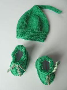 $25 Petit Pois est un ensemble Bonnet & Chaussons idéal pour l'automne et le printemps. Ses petits chaussons verts sont en laine acrylique. Les semelles extérieures sont en tissu à carreaux vert et blanc alors que l'interieur est en polaire blanc pour bien tenir chaud bébé. Les lacets de tissu permettent de bien maintenir la cheville de bébé. Le bonnet de lutin est assorti aux chaussons. Il s'agit d'une taille naissance.