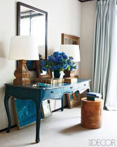 A beautifully painted French provincial desk, paired with blue works of art, pale-blue curtains, and blue hydrangea.