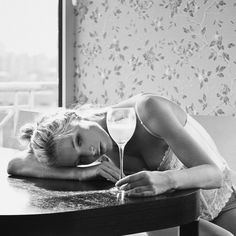 Hotel Noir | Photographer & Muse. Young woman resting her head on a table and handling a glass of cold drink.