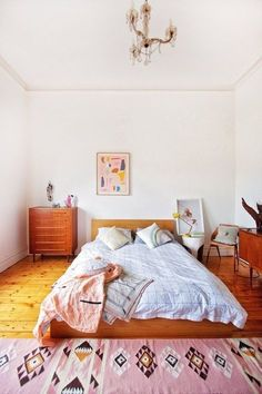 Modern southwest boho style in a bedroom design with a white, pink, and wood tone color scheme featuring mid-century modern furniture, contemporary art in pastel colors, and a pink, white, tan, yellow, and black patterned southwestern area rug - Home Decor & Decorating Ideas - apartmenttherapy.com