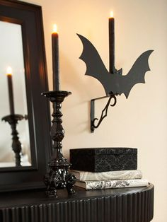 Give flight to a basic wall bracket by making a faux bat sconce. Wrapped books and a shiny black candlestick offer worthy mantel companions.