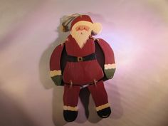 """Wooden Hand Painted Santa This wooden Santa is hand painted. He's legs and arms are attached with rope/jute which make them swing. You can use the rope/jute hanger to add him to your Christmas tree. He is approx. 8 1/2"""" tall. He does have some wear and the drilled holes from the rope are a little rough."""