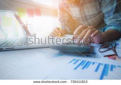 Businessman financial hand writing on notebook and do math on calculator to calculate big data report, accountancy document and laptop computer at office. Business finance concept.