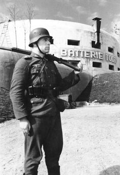 A German soldier stands guard in front of a defensive work at Cap Gris Nez, France. It was built by the Organisation Todt as part of the Atlantic Wall, 1942.
