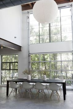 white lighting floor-to-ceiling windows grey tub chairs 8-seater dining table