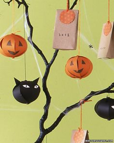 Homemade paper ornaments for Halloween tree.  Tree made by spray painting manzanita branches black.